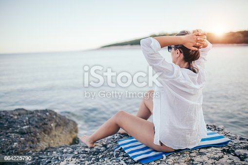 A photo of a woman practicing yoga on the rocky beach