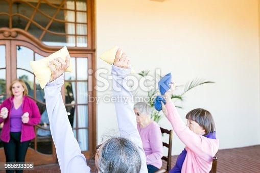 1047537292 istock photo Exercise class with senior women, arms raised 985893398