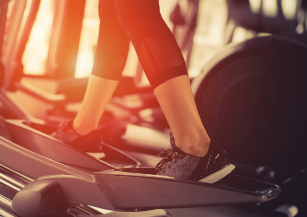 exercise elliptical cardio running workout at fitness gym of woman taking weight loss with machine aerobic for slim and firm healthy lifestyle in the morning. - ellipse stock photos and pictures