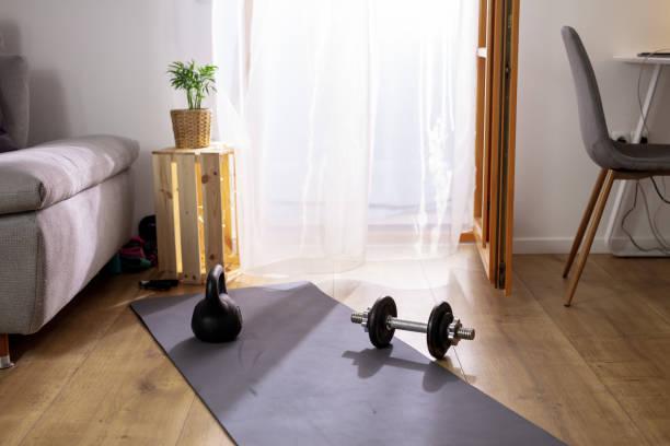 Exercise equipment on yoga mat in living room stock photo