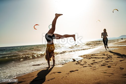 Two young female friends running on beach on sunny summer day