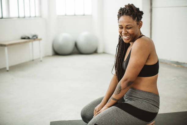 Exercise makes me smile Young women practicing yoga in gym. body positive stock pictures, royalty-free photos & images