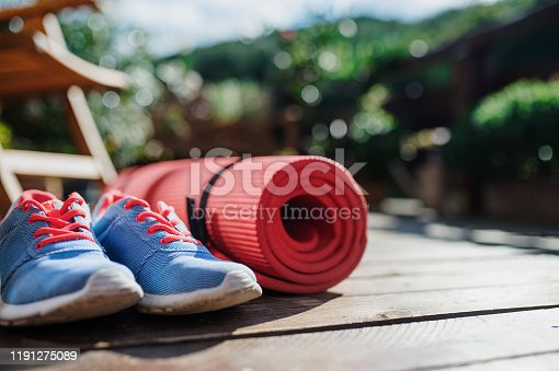 Composition of exercise mat and trainers outdoors on a terrace in summer.