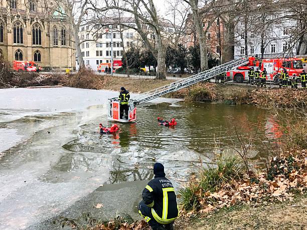 exercise of rescuing a man breaking into frozen lake in - feuerwehrmann deutsch stock-fotos und bilder