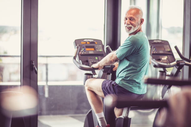 Exercise on bike at gym. Senior man at gym driving bike and looking at camera. exercise bike stock pictures, royalty-free photos & images