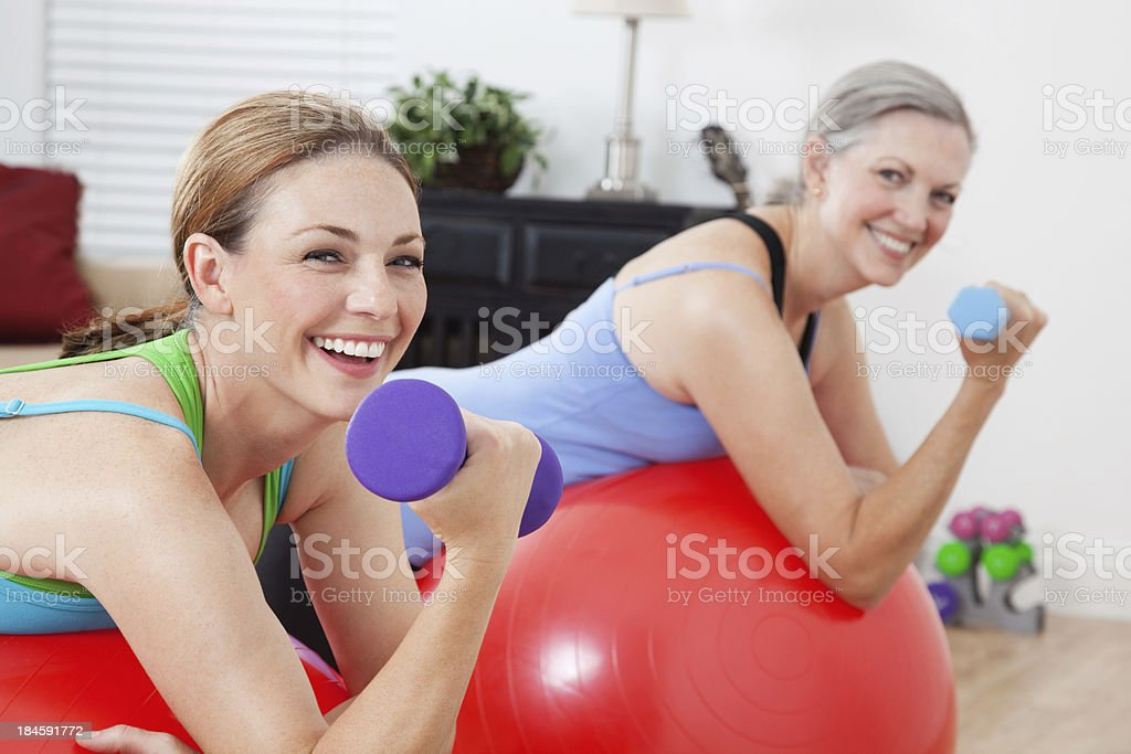 Exercise partners lifting weights on ball in home living room royalty-free stock photo