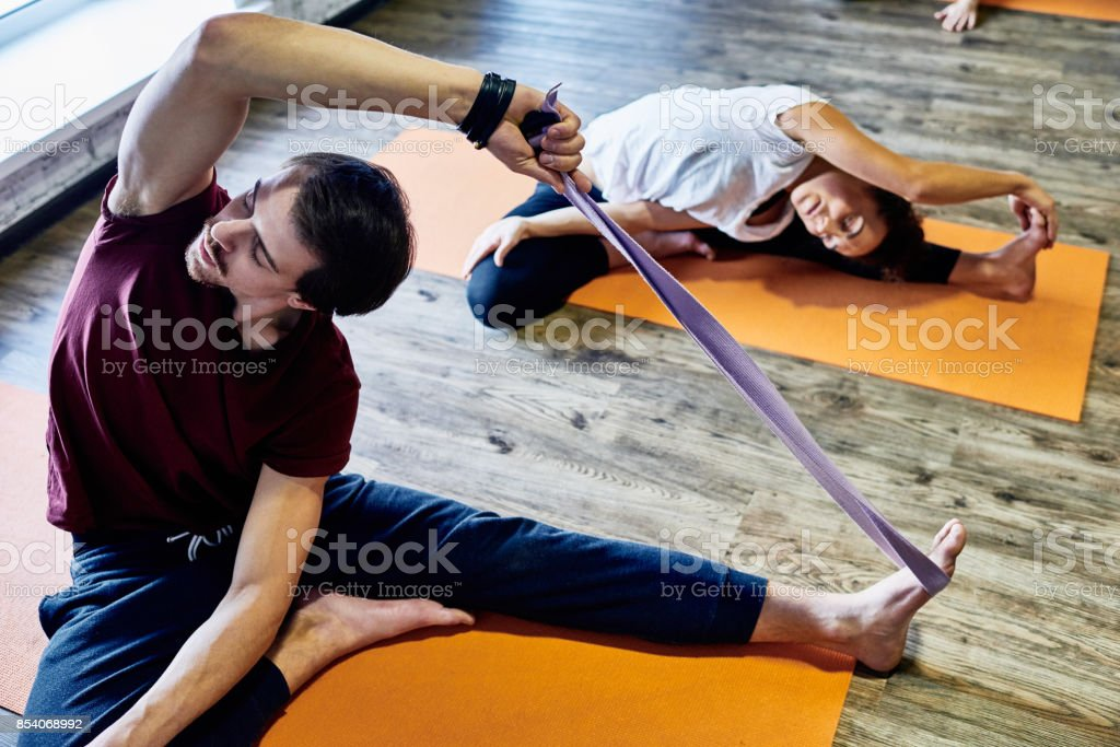 Concentrated young man visiting yoga class and trying to stretch on...