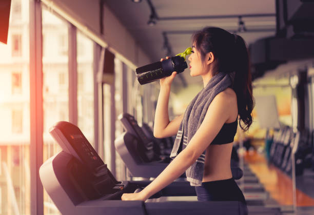 exercise treadmill cardio running workout at fitness gym of woman taking weight loss with machine aerobic for slim and firm healthy in the morning with drinking protein shake. - runner rehab gym foto e immagini stock