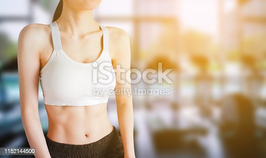 Exercise Workout. Young Woman Wearing White Sport Bra and Pants with Muscular Body and Strong Six Pack Abs in Gym Fitness. Sexy Fit Female Posing in Sports Clothes. Concept of Healthy Lifestyle.
