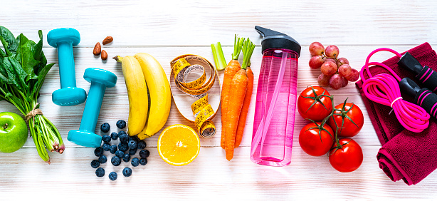 Exercising and healthy eating concept: overhead view of rainbow colored dumbbells, jump rope, water bottle, towel, tape measure and healthy fresh organic vegetables, fruits and nuts arranged side by side on white background. The composition includes spinach, tomato, carrot, banana, apple, blueberry, almonds, orange, celery, grape among others. High resolution 29Mp panoramic format studio digital capture taken with SONY A7rII and Zeiss Batis 40mm F2.0 CF lens