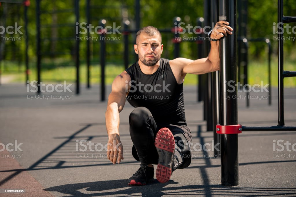 Young muscular athlete sitting on squats with left leg stretched...