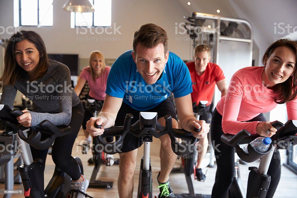 exercising class on exercise bikes at a gym looking stock photo
