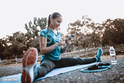 Sensual Female Athlete Stretching In Park While Listening To Music