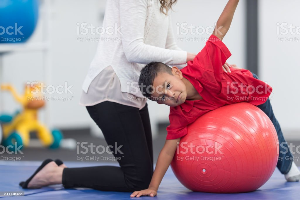 Cute young Hispanic boy doing recovery exercises with physical...