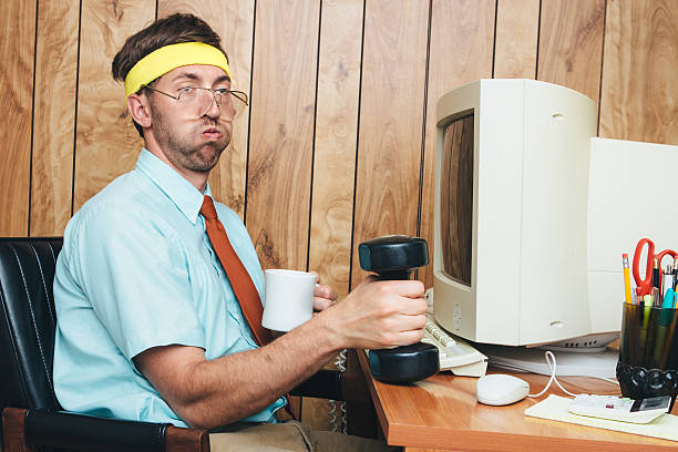 Exercising Office Worker A man and office in 1980's - 1990's style, complete with vintage computer and technology of the time, lifts some small hand weights, getting a short exercise break while remaining at his desk.  He wears a sweatband on his head, taking a short breather from his weight training and drinking some coffee.  Wood paneling on the wall in the background.  Horizontal image. nerd stock pictures, royalty-free photos & images