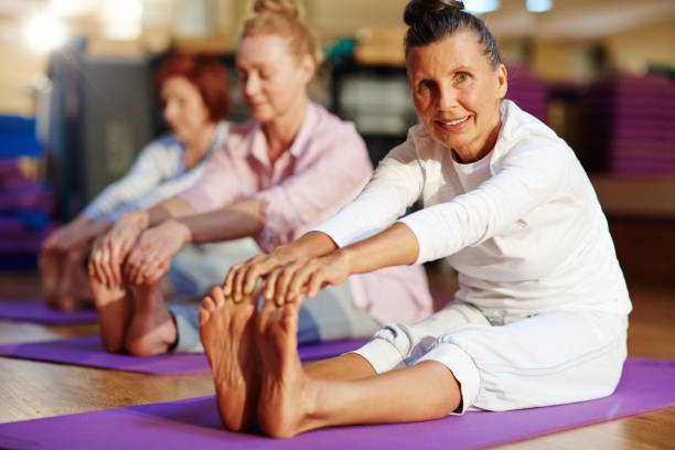 exercising on mats - active seniors stock photos and pictures