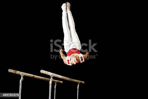 Young man doing exercises on parallel bars. He is in mid air. Isolated on black.