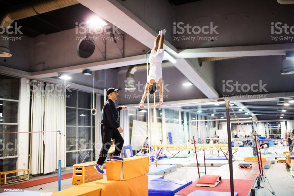 Exercising on uneven parallel bars with trainer stock photo