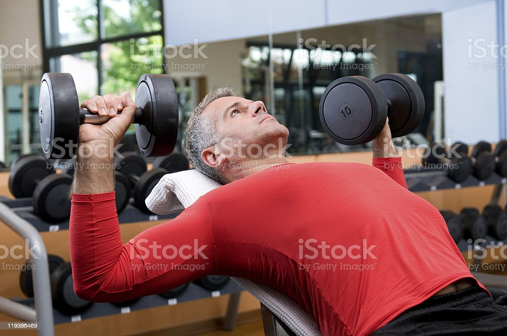 Exercising with dumbells at gym stock photo