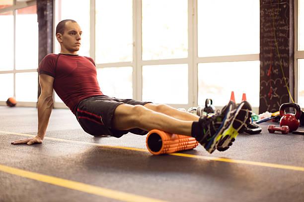 ejercite con rodillo de espuma en el gimnasio - atleta papel social fotografías e imágenes de stock