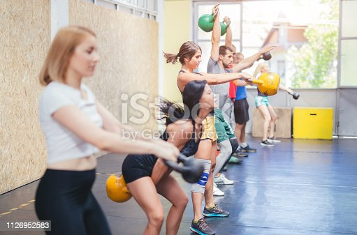 Group of people exercising with kettlebells