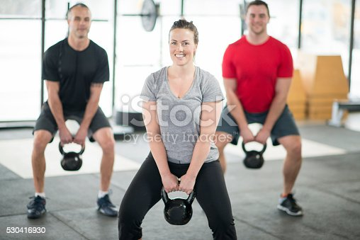 A group of young adults are lifting kettlebells together at the gym.