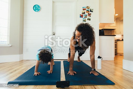 A mother exercises with her young son inside their home. She is teaching the boy the importance of a healthy lifestyle by proper stretching and exercising.