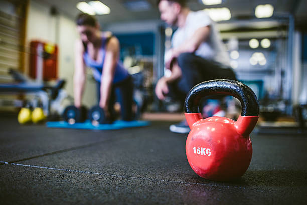 exercising with personal trainer - exercise equipment stock photos and pictures