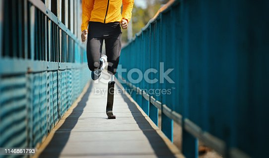 Closeup front view of mid 20's unrecognizable man with carbon fibre prosthetic limb jogging on a sunny day over a footbridge.