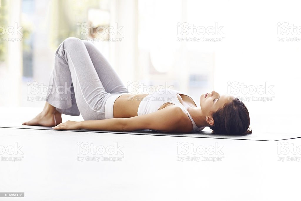 Exercising - Young fitness woman lying on a yoga mat royalty-free stock photo