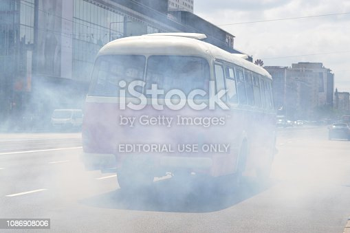 Warsaw, Poland - 19th May, 2018: Smoke billows from the old bus. The air pollution is one of the most important problems in the cities.