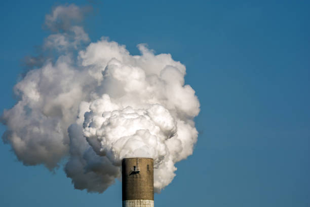 exhaust gases and pollutants by the industry using the example of a smoky chimney - azoto foto e immagini stock