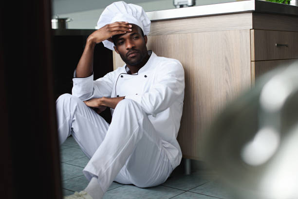 exhausted african american chef sitting on floor at restaurant kitchen and looking away - chef triste foto e immagini stock