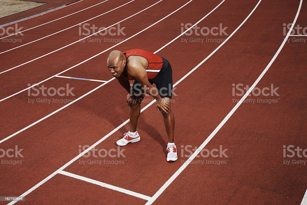 Exhausted African American man on running track stock photo