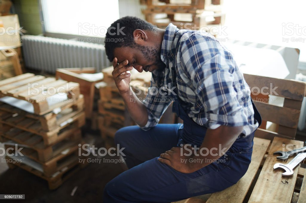 Exhausted African employee in warehouse stock photo