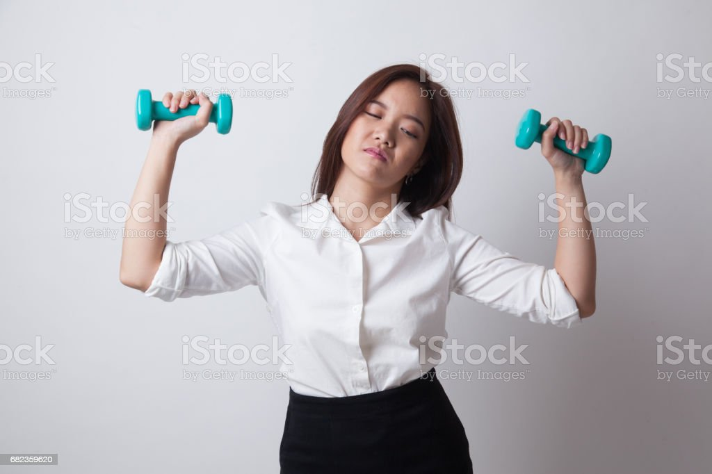 Exhausted Asian woman with dumbbells. foto stock royalty-free