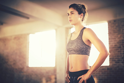 Exhausted attractive female with hands on hips in gym. Tired young female is wearing sports bra showing abdomen muscles. She is standing in health club.