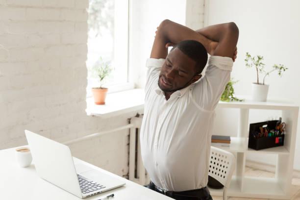erschöpft schwarze arbeiter büro turnen im stuhl bei workp - yoga fürs büro stock-fotos und bilder