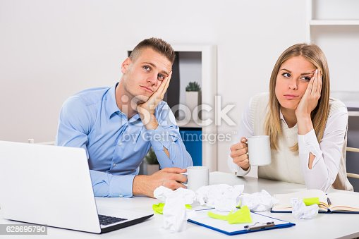 istock Exhausted businessman and businesswoman drinking coffee 628695790