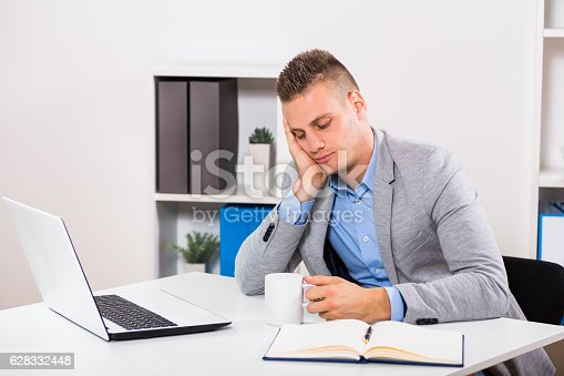 istock Exhausted businessman  drinking coffee 628332448