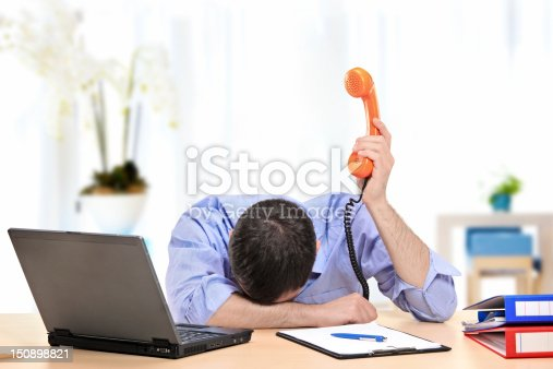 istock Exhausted businessman holding a telephone in his office 150898821