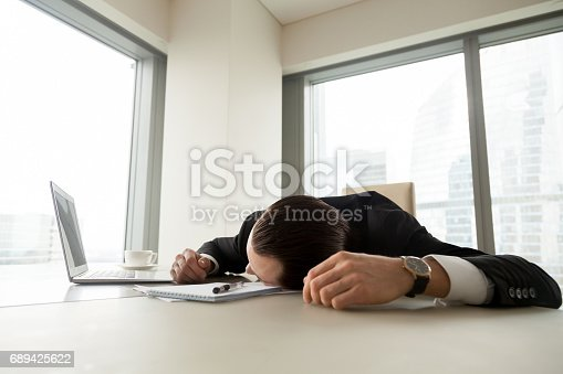 istock Exhausted businessman lying on his desk in office 689425622