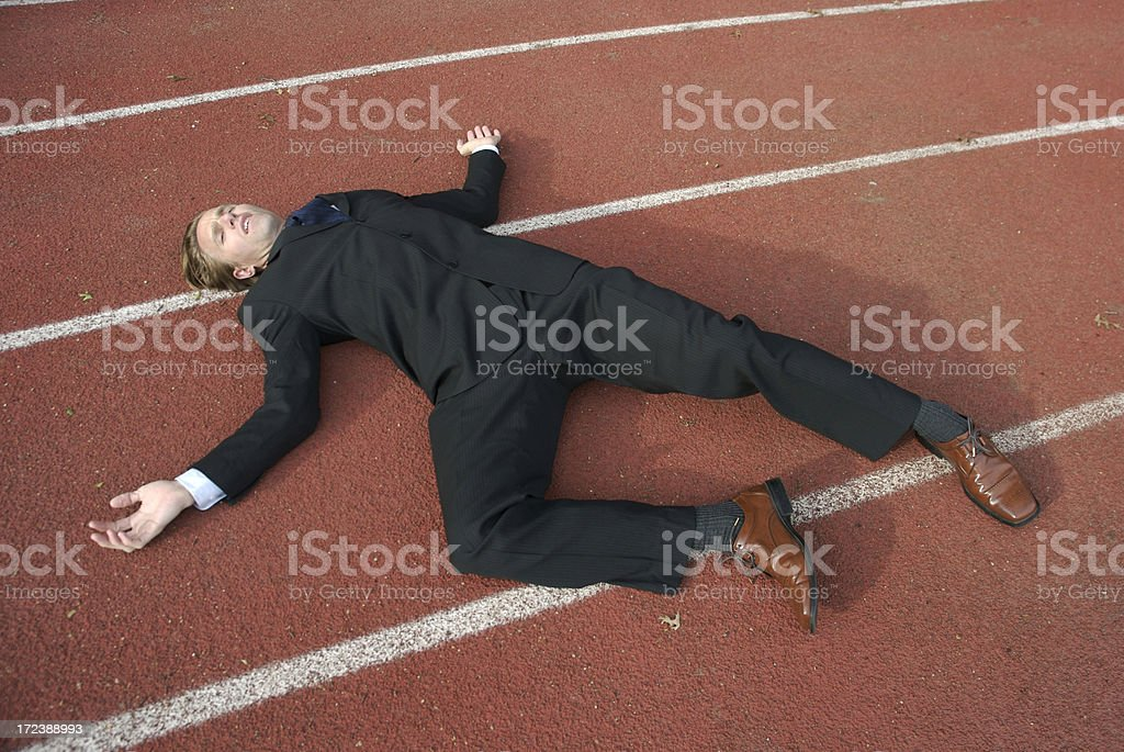 Exhausted Businessman Lying on Sports Track stock photo