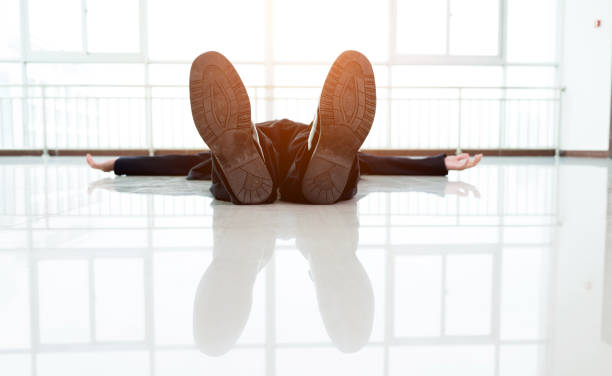 Exhausted businessman lying on the floor stock photo