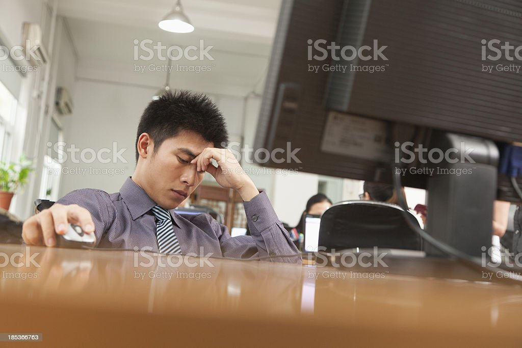 Exhausted businessman sitting in front of computer royalty-free stock photo