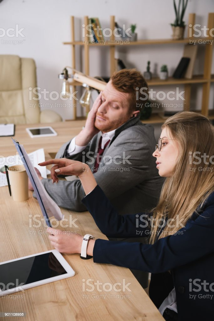 exhausted businesspartners lookign at documents together at office stock photo