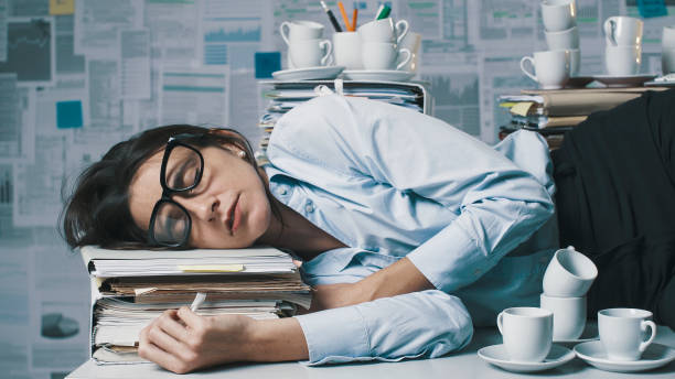 Exhausted businesswoman lying down on the desk and sleeping stock photo