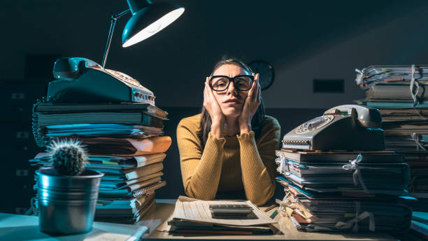 Exhausted businesswoman working late at night stock photo