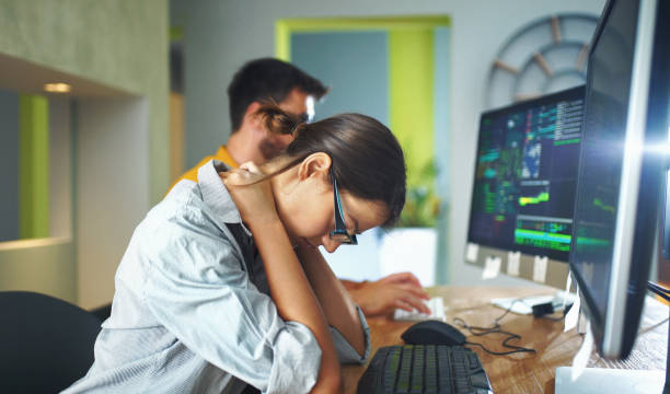 Exhausted by office work. Closeup side view of couple of mid 20's software developers resolving some issues with the code they're currently working on. The woman is in focus and she's experiencing some neck and back pain. bad posture stock pictures, royalty-free photos & images