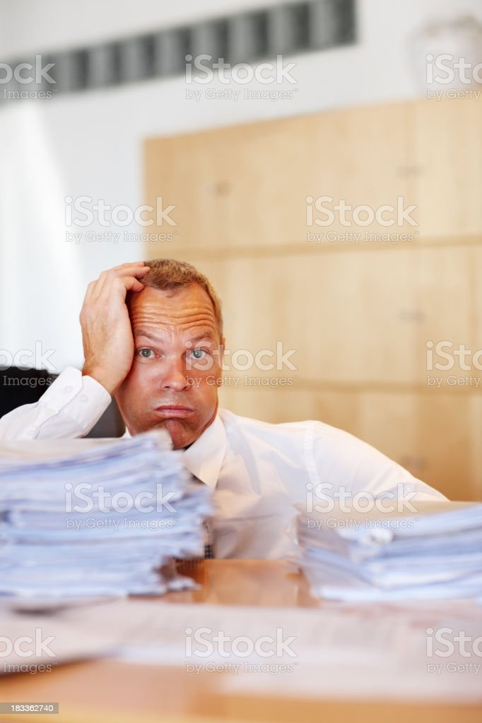 Exhausted clerk sitting with head in hand royalty-free stock photo